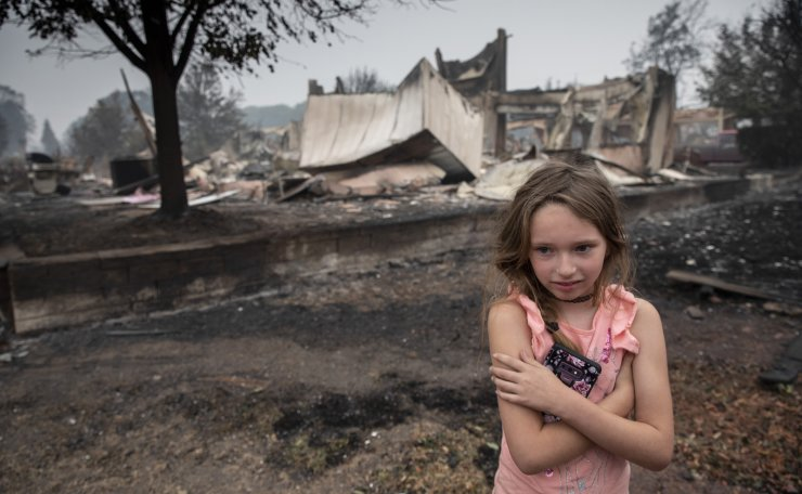 Ellie Owens, 8, from Grants Pass, Ore., looks at fire damage Friday, Sept. 11, 2020, as destructive wildfires devastate the region in Talent, Ore. AP