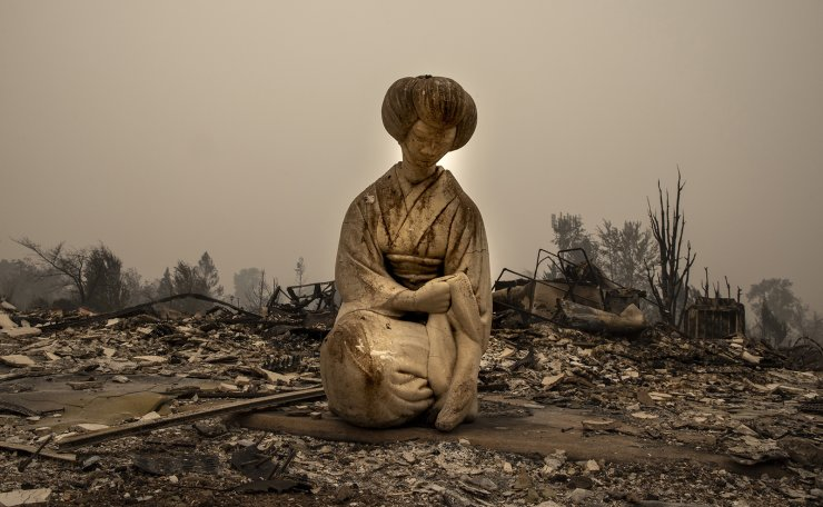 A Japanese style statue is seen in a destroyed neighborhood as destructive wildfires devastate the region on Friday, Sept. 11, 2020, in Talent, Ore. AP