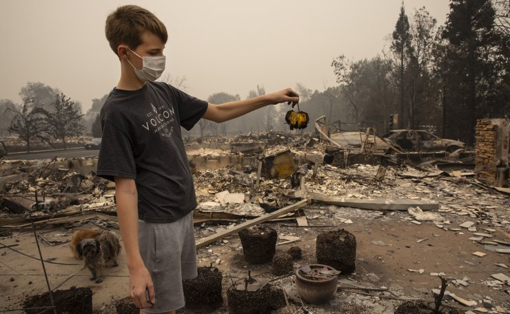 Jacen Sullivan, 14, from Talent, Ore., holds a burned tomato he found in the garden at his burned home in Talent on Friday, Sept. 11, 2020, as destructive wildfires devastate the region. AP