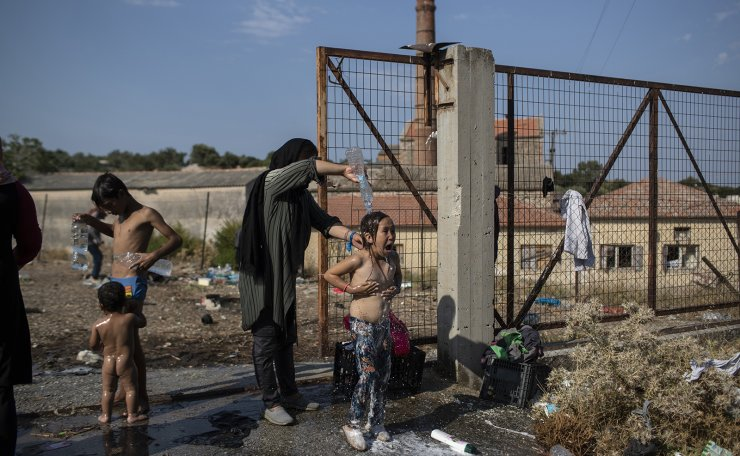 A woman washes a girl as migrants gather near Mytilene town, on the northeastern island of Lesbos, Greece, Saturday, Sept. 12, 2020. AP