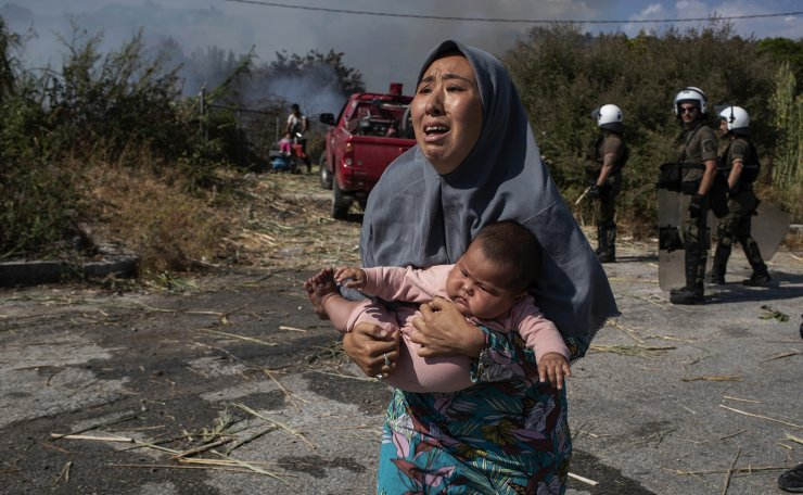 A migrant holds her baby as she runs to avoid a small fire in a field near Mytilene town, on the northeastern island of Lesbos, Greece, Saturday, Sept. 12, 2020. AP