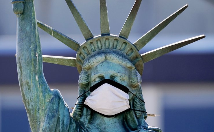 In this Aug. 26, 2020, file photo, the face on a replica of the Statue of Liberty covers with a protective face mask against the coronavirus. The 1/18th scale replica on Seattle's Alki Beach was erected in 1952 and recast in 2006. AP