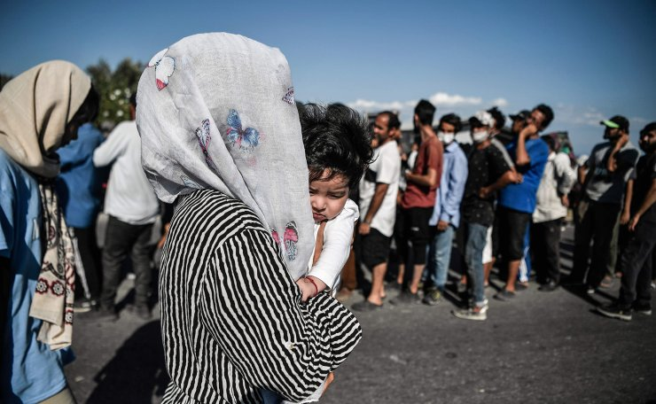 A woman with her baby walks past a queue during food distribution along a road where thousands of refugees and migrants are living with out shelter and exposed to the elements following the burning down of their camp, near the Kara Tepe camp on the island of Lesbos on September 13, 2020. AFP