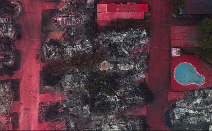 Red fire retardant blankets burned residences, vehicles and a swimming pool in the aftermath of the Almeda fire in Talent, Oregon, U.S., September 13, 2020. Picture taken with a drone. Reuters