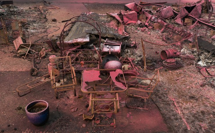 The skeletons of a table and chairs are seen covered in red fire retardant in the aftermath of the Almeda fire in Talent, Oregon, U.S., September 14, 2020. Reuters