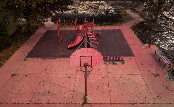 Red fire retardant blankets a basketball post and a playground in the aftermath of the Almeda fire in Talent, Oregon, U.S., September 14, 2020. Picture taken with a drone. Reuters