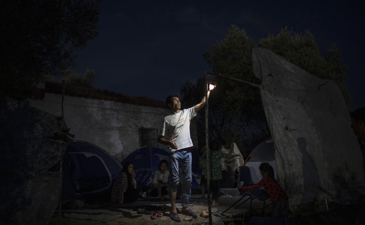 An Afhan man repairs a light as he and other refugees and Migrants are sheltered near the destroyed Moria camp on the island of Lesbos, Greece, on Wednesday, Sept. 16, 2020. AP