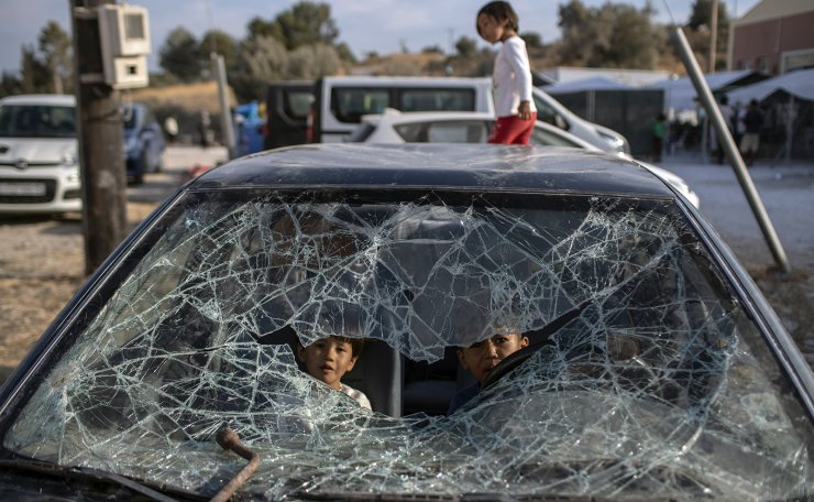 Afghan children play inside an abandoned car as refugees and migrants from the destroyed Moria camp are sheltered, near a new temporary camp, on the island of Lesbos, Greece, on Wednesday, Sept. 16, 2020. Greek officials have said they could forcibly remove people from the road near the burned-out camp where they have been sleeping rough and take them to the camp if people refuse to go. AP