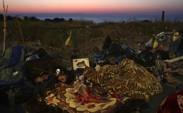 Migrants sleep in a camp on a road leading from Moria to the capital of Mytilene, on the northeastern island of Lesbos, Greece, Thursday, Sept. 17, 2020. Fires swept through the overcrowded camp at Moria on two nights the previous week, prompting more than 12,000 migrants and refugees to flee. Most of them remain without shelter even though emergency tents are available at another island site where a new camp is being built. AP