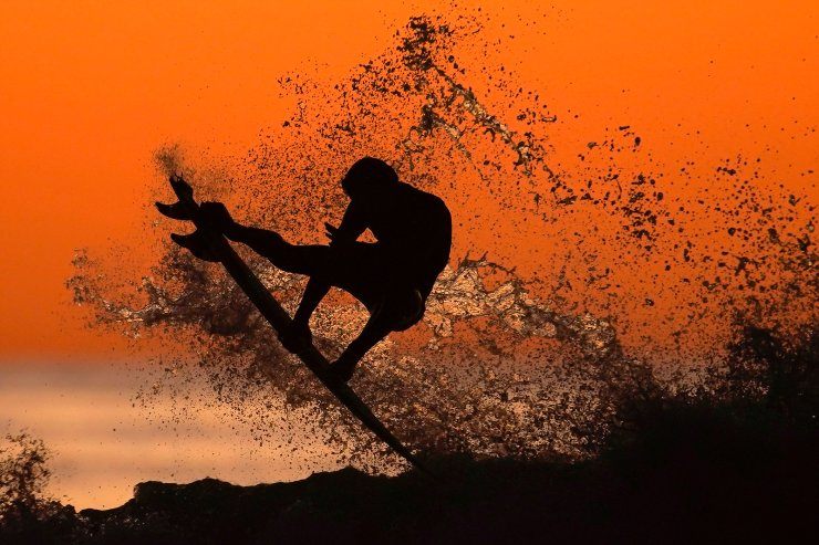 A surfer takes some air off a wave while surfing after sunset in Cardiff, California, U.S., January 7, 2020.  REUTERS/Mike Blake