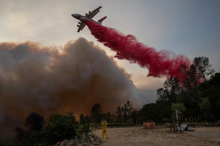 A woman wearing flame-resistant clothing photographs an airplane as it drops red fire retardant on the Glass Fire at a vineyard in Deer Park, California, U.S. September 27, 2020. REUTERS/Adrees Latif