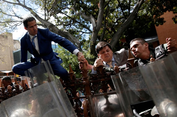 Venezuelan opposition leader Juan Guaido, who many nations have recognised as the country's rightful interim ruler, and other lawmakers climb on the fence of Venezuela's National Assembly building in Caracas, Venezuela, January 5, 2020. REUTERS/Manaure Quintero