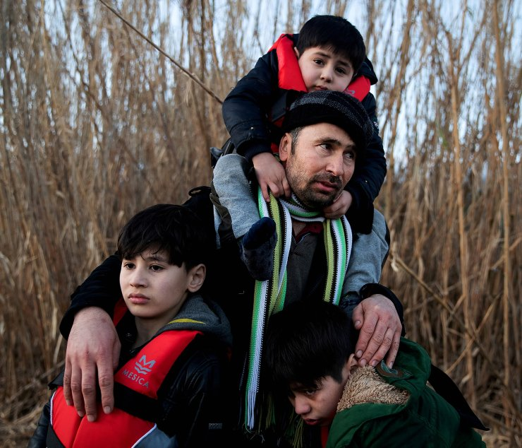 A man holds his three sons as migrants from Afghanistan arrive on a dinghy on a beach near the village of Skala Sikamias, after crossing part of the Aegean Sea from Turkey to the island of Lesbos, Greece, March 2, 2020. REUTERS/Alkis Konstantinidis