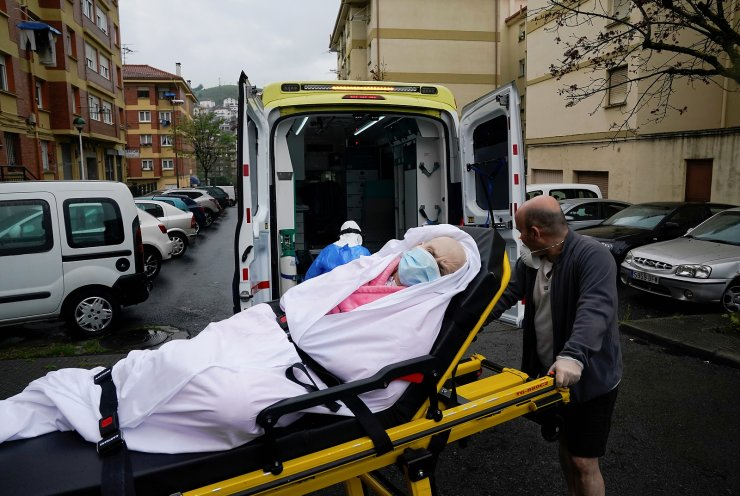 Coronavirus patient Maria Josefa Arias, 76, is lifted into an Ambuiberica ambulance by her son Ander Maria Dominguez Arias and emergency technician Marisa Arguello de Paula during the coronavirus disease (COVID-19) outbreak, in Llodio, Spain, April 19, 2020. REUTERS/Vincent West