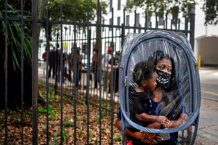 Dana Clark and her 18-month-old son Mason wait in line at City Hall as early voting begins for the upcoming presidential election in New Orleans, Louisiana, U.S., October 16, 2020. Clark said she donned this protective cover because she didn't know how many people would be wearing masks in line, and her child doesn't have a mask. She said she works as a teacher, and wanted to take precautions for her students' sakes. REUTERS/Kathleen Flynn