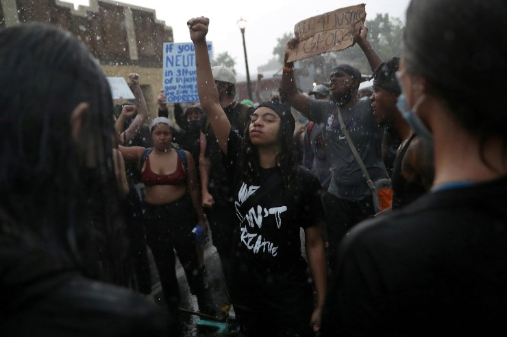 Rain falls as Monie Scott raises her fist while people chant around her at a memorial site for George Floyd that has been created at the place where he was taken into police custody and later pronounced dead, in Minneapolis, Minnesota, U.S., June 2, 2020. REUTERS/Leah Millis