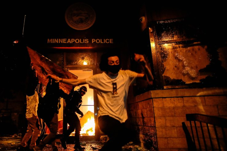 Protesters react as they set fire to the entrance of a police station as demonstrations continue in the aftermath of the death in Minneapolis police custody of George Floyd, in Minneapolis, Minnesota, U.S., May 28, 2020. REUTERS/Carlos Barria