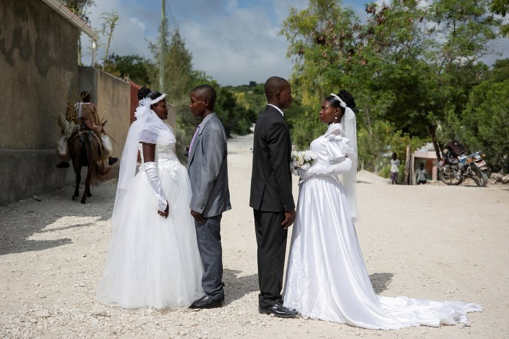 Patricia, who is pregnant, and Obelson, who got married in a joint ceremony with another pregnant couple who they did not know to share the costs of the ceremony, pose for a photo outside the church where they got married in Baie de Henne, Nord Ouest Department, Haiti, October 27, 2018. REUTERS/Valerie Baeriswy