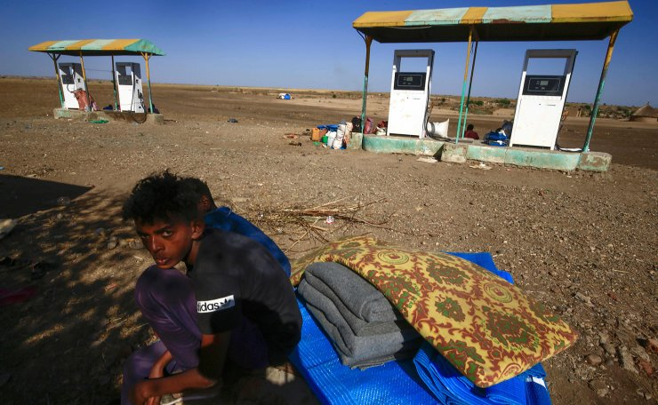 Ethiopian refugees who fled the fighting in the Tigray region sit in the shade at a reception center in the Hamdayit area of Sudan's eastern Kassala state, on November 22, 2020. The placard reads 'stop for inspection'. AFP