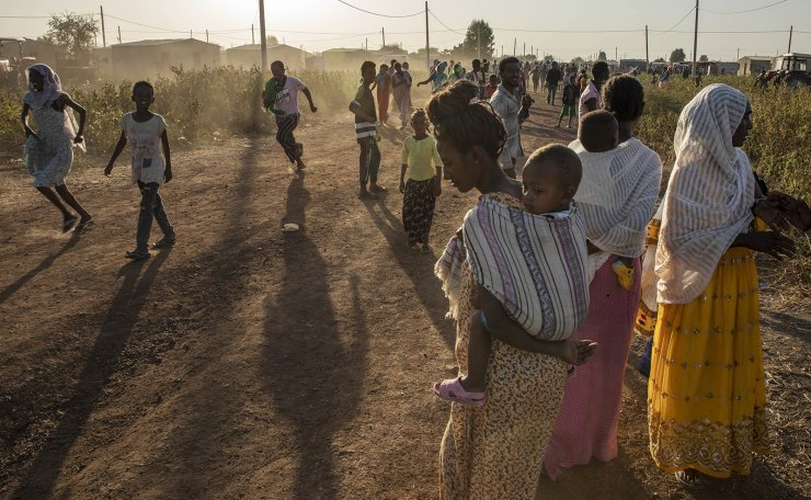 Tigray refugees who fled a conflict in the Ethiopia's Tigray region, run at Village 8, the transit centre near the Lugdi border crossing, eastern Sudan, Sunday, Nov. 22, 2020. AP