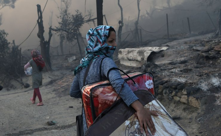 A migrant carries her belongings following a fire at the Moria camp for refugees and migrants on the island of Lesbos, Greece, September 9, 2020. REUTERS