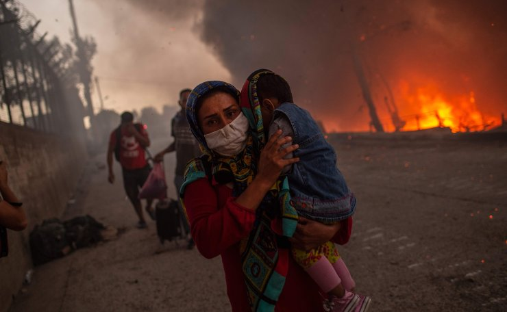 A woman carries a child past flames after a major fire broke out in the Moria migrants camp on the Greek Aegean island of Lesbos, on September 9, 2020. - Thousands of asylum seekers were left homeless on on September 9 after a fire gutted Greece's largest migrant camp on Lesbos, plunging the island into crisis and provoking an outpouring of sympathy from around Europe and calls for reform of the refugee system. The blaze, which began hours after 35 people tested positive for coronavirus at the Moria camp, sent thousands fleeing for safety into surrounding olive groves -- but nobody was seriously hurt. AFP