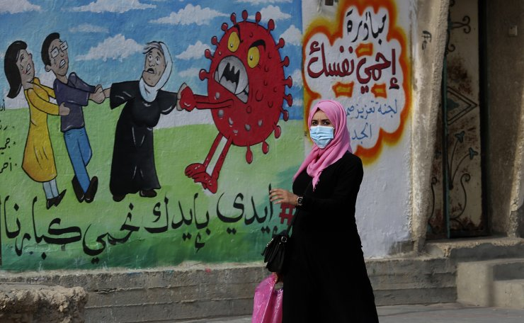 A woman walks past a mural encouraging the wearing of face masks amid the coronavirus pandemic, on the main road of Nusseirat refugee camp, central Gaza Strip, Tuesday, Nov. 24, 2020. Arabic reads: 'protect yourself, together we protect the old.' AP