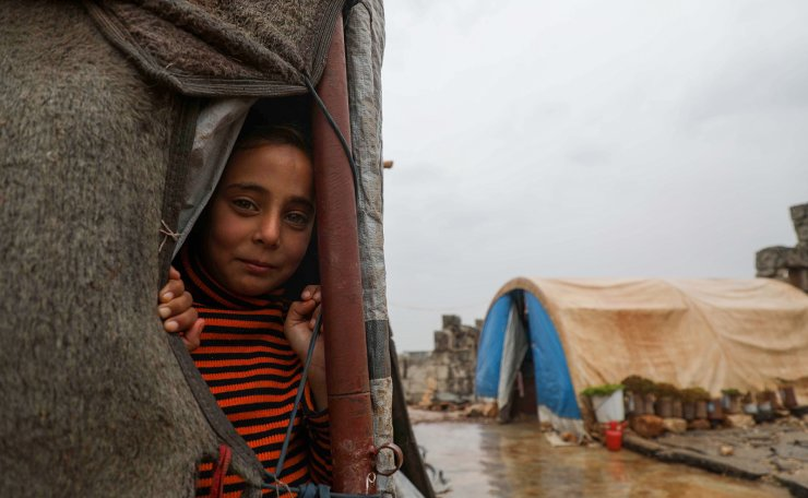 A displaced Syrian child poses for a picture from a tent at a makeshift camp after heavy rainfall at the UNESCO-listed site of Babisqa filled with abandoned ancient settlements in northwestern Syria, near the Turkish border, on November 26, 2020. AFP