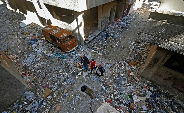 Issa al-Loubani, a 48-year-old Palestinian refugee, walks with his wife and daughter in a street in the Palestinian Yarmuk camp, on the southern outskirts of the Syrian capital Damascus, on November 25, 2020. AFP