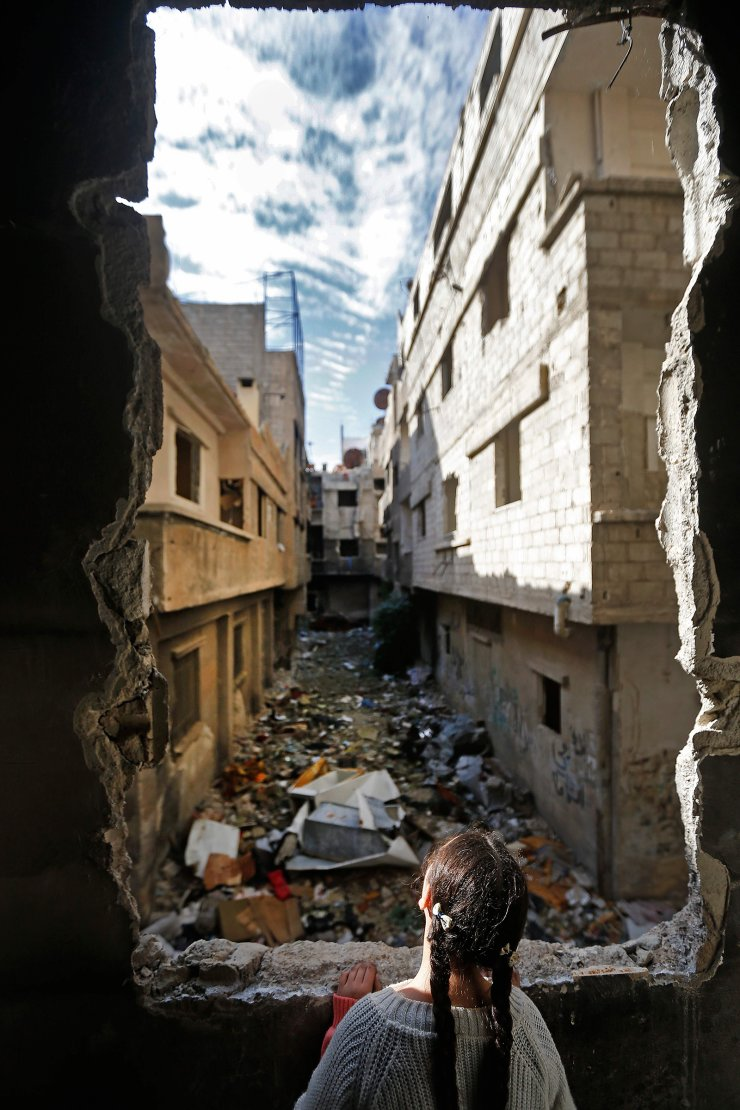 Shatha, the daughter of 48-year-old Palestinian refugee Issa al-Loubani, looks out the window of their apartment in the Palestinian Yarmuk camp, on the southern outskirts of the Syrian capital Damascus, on November 25, 2020. - When Syrian authorities said they would allow returns to the war-ravaged Yarmuk camp for Palestinian refugees in southern Damascus, Issa al-Loubani rushed to sign up and quickly started repairing his home. Loubani, who first left in 2012, is determined to join their ranks even if the windows of his wrecked apartment are still covered with plastic sheeting. AFP