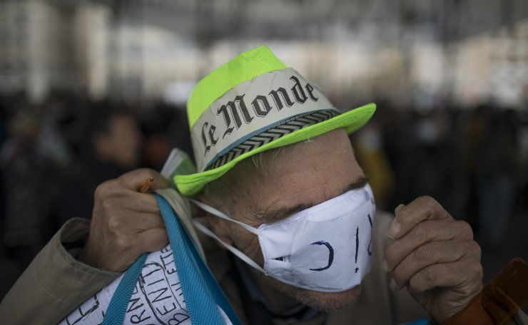 A protester covers his face with a mask during a demonstration against a security law that would restrict sharing images of police, Saturday, Nov. 28, 2020 in Marseille. AP