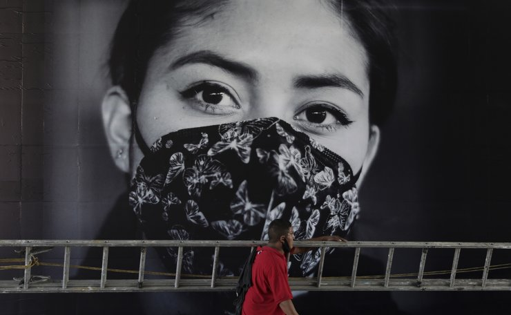 A man hauling a ladder walks past a government advertisement inviting citizens to wear protective face masks amid the new coronavirus pandemic, in Mexico City, Saturday, Nov. 28, 2020. AP