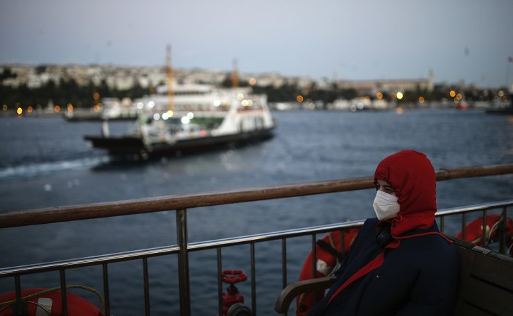 In this Wednesday, Oct. 21, 2020, file photo, a woman, wearing a protective mask to help prevent the spread of the coronavirus, takes a boat trip over the Bosphorus Strait separating the Asian and the European sides of Istanbul. AP