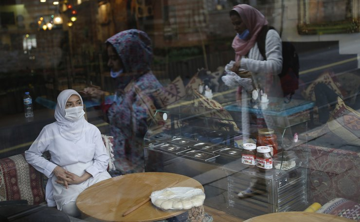In this Wednesday, March 25, 2020, file photo, a customer wearing a protective mask due to the coronavirus outbreak, waits sits on a table of a restaurant, in central Istanbul.  AP
