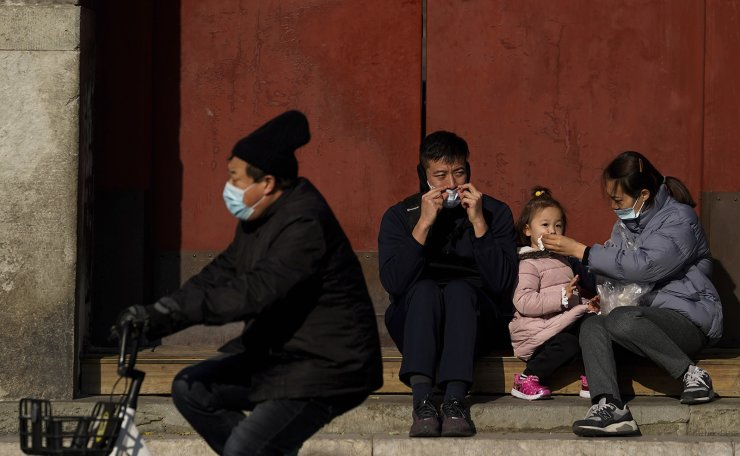 A man wearing a face mask to help curb the spread of the coronavirus cycles pass family members take a rest outside the drum tower, a tourist spot in Beijing, Sunday, Nov. 29, 2020. AP