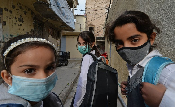 Iraqi pupils wearing protective masks walk to school on the first day of the new academic year the northern city of Mosul, on November 29, 2020, amid the COVID-19 pandemic. AFP