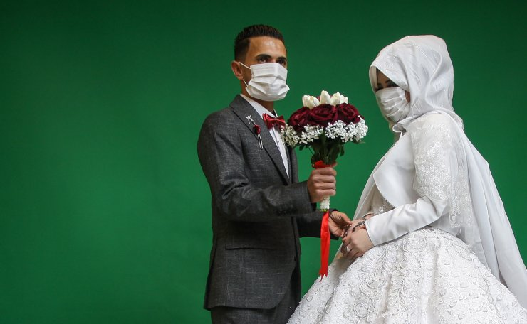 Palestinian groom Mohamed abu Daga, 24, and his bride Israa wear face masks amid the COVID-19 epidemic during a photoshoot before their wedding ceremony in Khan Yunis, southern Gaza, on Monday on March 23, 2020. UPI