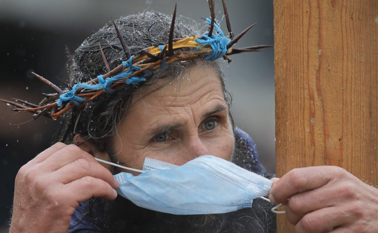 A man wearing a thorn crown adjusts his mask for protection against COVID-19, holds a wooden cross while attending a religious service celebrating St. Andrew in the village of Ion Corvin, eastern Romania, Monday, Nov. 30, 2020. AP