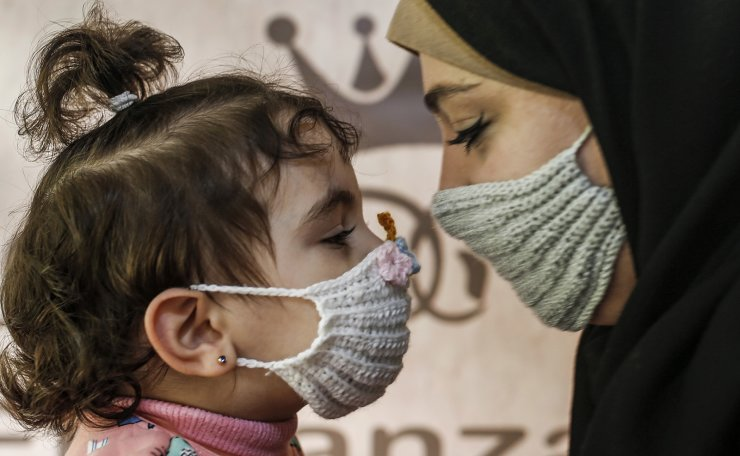 Nouran Faraj, a 24-year-old Palestinian, holds her niece as she dons a handmade crochet wool mask (prevention measure for the COVID-19 coronavirus pandemic) of her creation in Gaza City on December 1, 2020. AFP