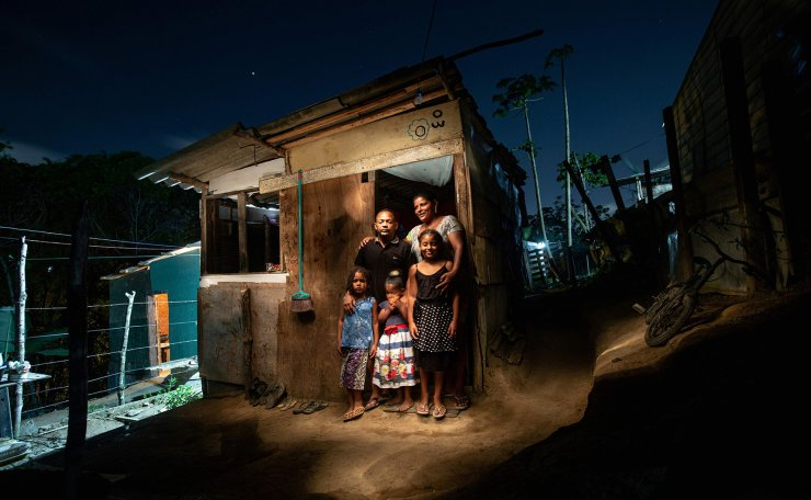 Antonio Pedro de Souza(2nd L), 42, -a painter who has been out of work since the beginning of the pandemic- poses for a picture next to his wife (R), Ilma da Silva Santos and their children at their home at Manuel Faustino squatter camp, near Salvador, Bahia, Brazil on October 16, 2020. AFP