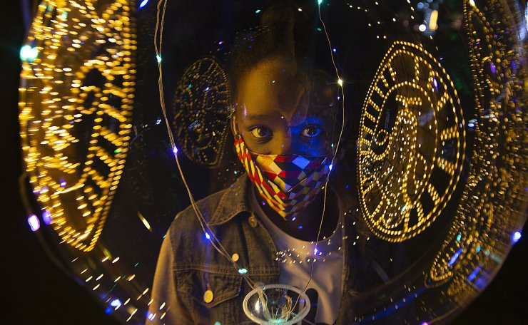 Christmas lights are reflected on a ballon as a child wears a face mask to protect against coronavirus at the Johannesburg Zoo's Festival of Lights Tuesday Dec. 1, 2020. AP