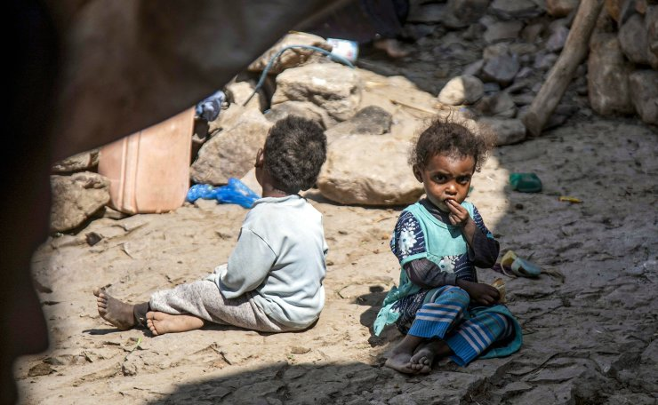 Children sit on the ground by a cave where a Yemeni family has sought refuge due to poverty and lack of housing, west of the suburbs of Yemen's third-city of Taez on December 2, 2020. AFP