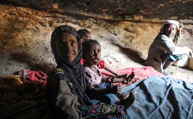 A man and children sit in a cave where a Yemeni family has sought refuge due to poverty and lack of housing, west of the suburbs of Yemen's third-city of Taez on December 2, 2020.  AFP