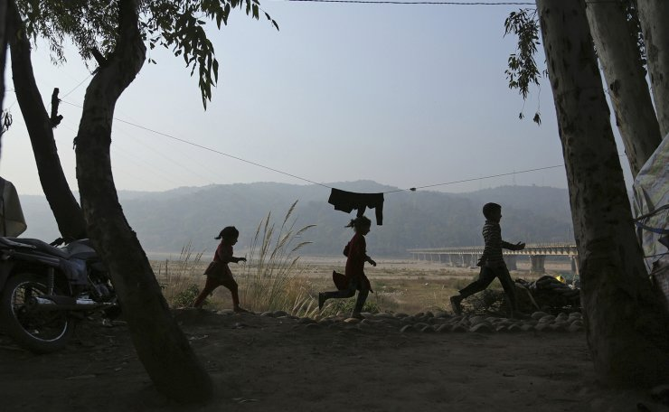 Indian nomadic Gujjar children play at a temporary shelter on the outskirts of Jammu, India, Thursday, Dec. 3, 2020. Nomadic Gujjars walk for miles with their cattle through the mountains during summer months in search of green pastures and move back to the plains with the advent of winter.  AP