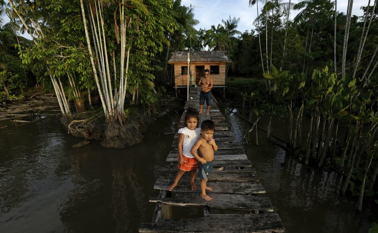 Luiz Carlos and their children walk on a pier in the Santa Luzia community, in the riverside regions of the city of Portel, located in the island of Marajo, Para state, on the mouth of the Amazon river, Brazil, Friday, Dec. 4, 2020. The municipality of Portel has one of the lowest human development rates in the country, concentrating a population with low levels of prevention and use of protective masks for COVID 19. Brazil is expecting a second wave of COVID-19 cases nationwide, with the state of Para reporting high numbers of people infected and more than 63 thousand dead from the disease so far. AP