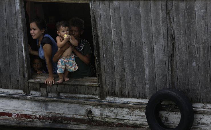 Children without a protective masks for COVID 19 look out a window from of a boat in the port of the city of Portel, located in the island of Marajo, Para state, on the mouth of the Amazon river, Brazil, Friday, Dec. 4, 2020. AP