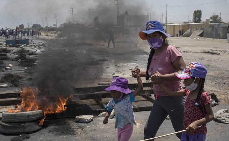 A woman and children walk past a burning barricade on a stretch of Pan-American South Highway, on the sixth day of protests by farmworkers in Villacuri, Ica province, Peru, Saturday, Dec. 5, 2020. The farmworkers are demanding better pay and protesting clauses in a law that exempts them from benefits given other workers, including annual bonuses and vacations. AP