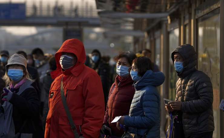 Commuters wearing face masks to help curb the spread of the coronavirus line-up to board a bus at a bus stand in Beijing, Sunday, Dec. 6, 2020. AP