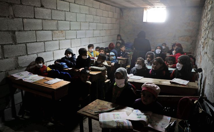 Syrian school children wearing masks due to the Covid-19 pandemic, sit at a makeshift school set up by locals in the village of Ma'arin on the outskirts of Azaz in the rebel-controlled northern countryside of Syria's Aleppo province, on December 8, 2020. AFP