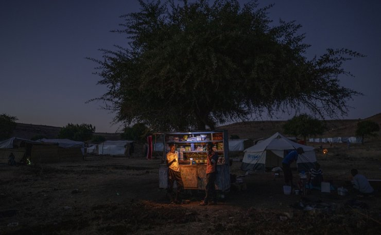 Tigrinyan refugee men sell goods in their shack to make a living at Umm Rakouba refugee camp in Qadarif, eastern Sudan, Friday, Dec. 11, 2020. AP